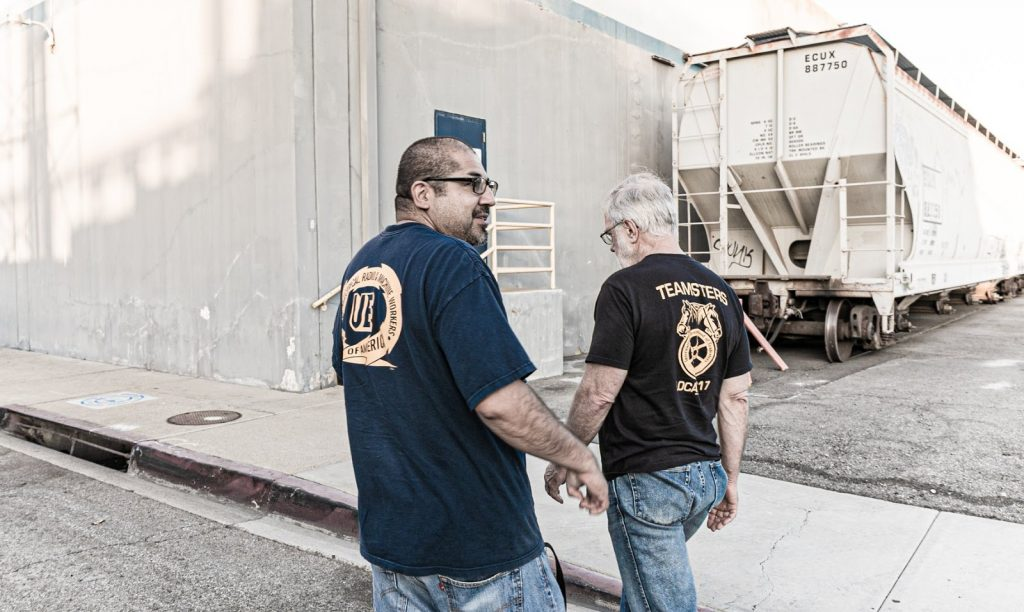 Howie and Fernando Ramirez are walking next to each other, both wearing union t-shirts, during a tour of chemical facilities in a predominantly Latino section of Los Angeles, September 23, 2019.