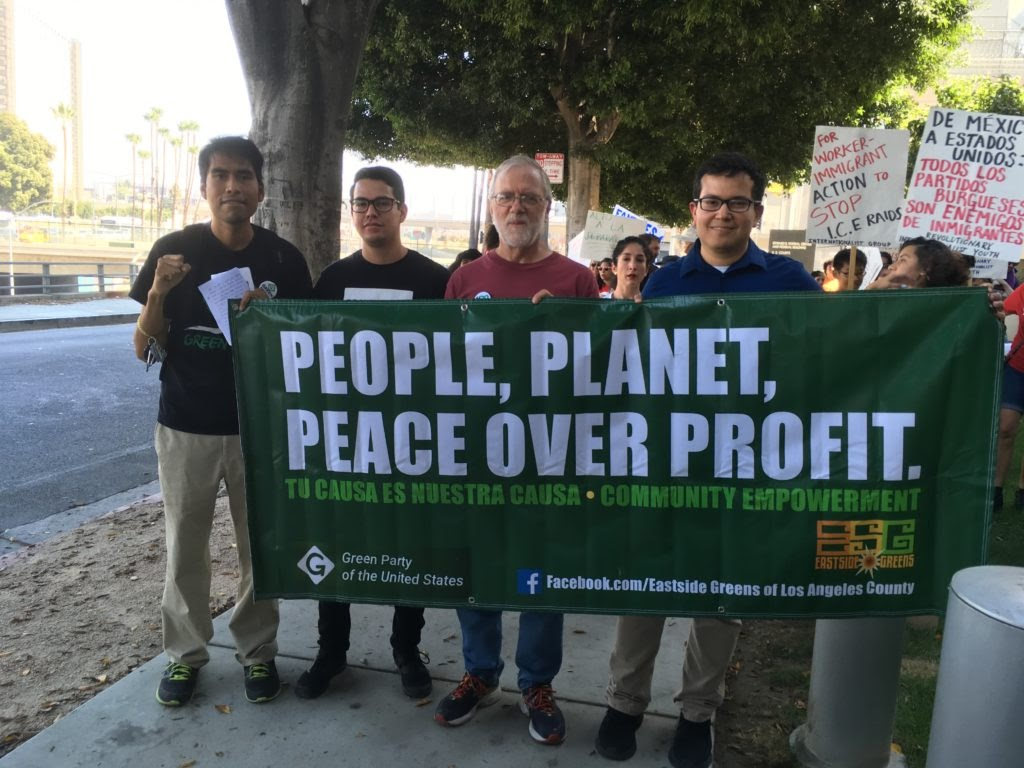 Howie is standing in a crowd of people, and they're all holding a green banner that says people planet peace over profit. From the Close the Camps march, October 12, 2019